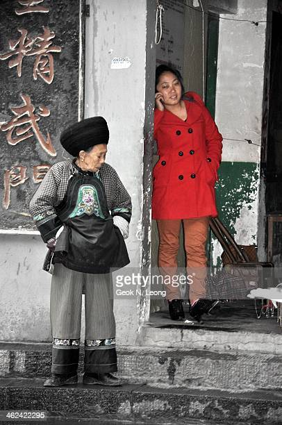 Young lady dress in red modern clothing talking on the mobile phone and an elderly woman with her hands in the pocket dressed in traditional chinese...
