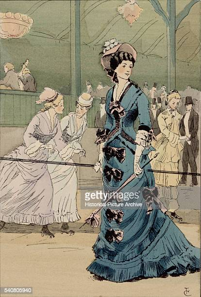 A young lady dressed in a corseted blue dress trimmed with bows leans on a barrier at the edge of the rink