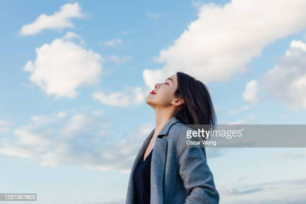 young lady embracing hope and freedom - zorgeloos stockfoto's en -beelden