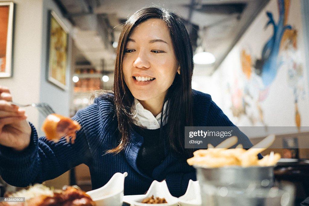 Young lady enjoying meal joyfully in a restaurant : Stock Photo