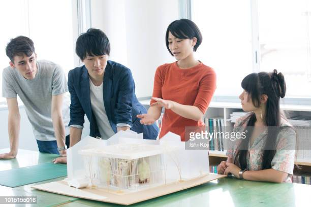 a young lady explaining the model of architecture - デザイナー ストックフォトと画像