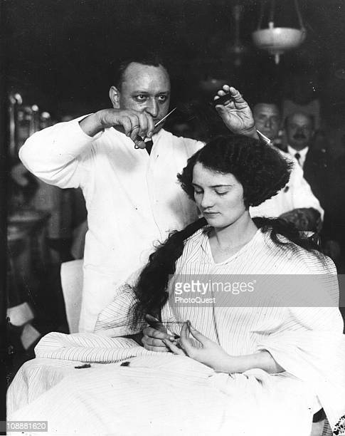 A young lady getting her hair bobbed in a men's barber shop early twentieth century