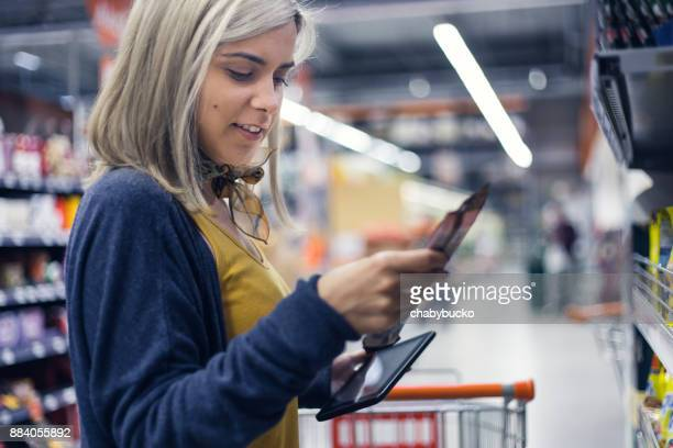 young lady groceries shopping - convenience store stock photos and pictures