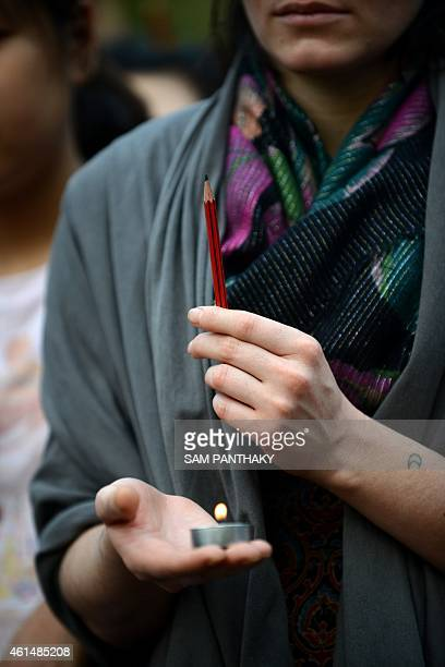 A young lady holding a candle and a pencil participates in a candlelight vigil near the statue of Mahatma Gandhi at Gandhi Ashram in Ahmedabad on...
