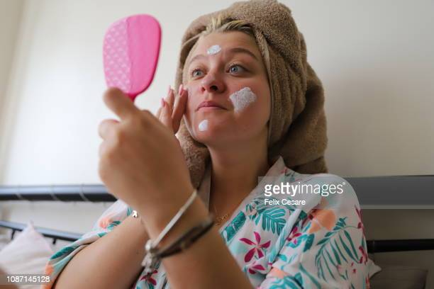 a young lady holding a little mirror and applying cream on her face after shower - jeune femme sous la douche photos et images de collection