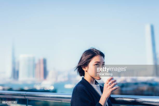 Young lady holding a takeaway coffee cup by the harbour