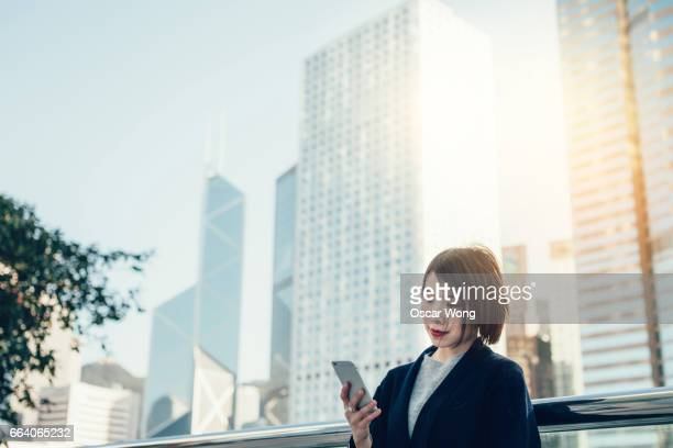 Young lady holding smartphone in park against cityscape