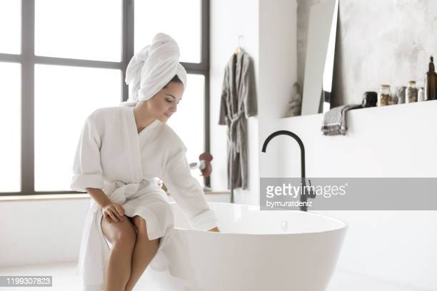 young lady in bathrobe touching water - bathtub stock pictures, royalty-free photos & images