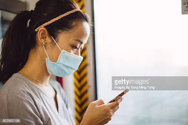 Young lady in face mask using smartphone on train
