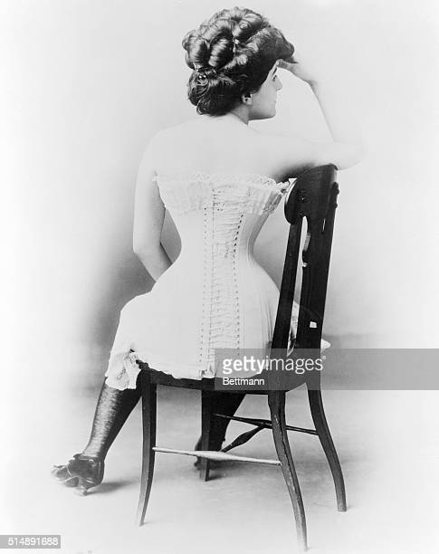 Young lady in victorian corset. Back view seated in chair. Undated photograph.