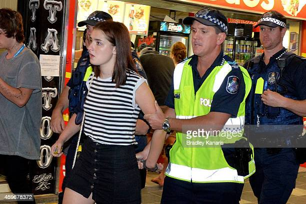 A young lady is arrested during Australian 'schoolies' celebrations following the end of the year 12 exams on November 28 2014 in Gold Coast...
