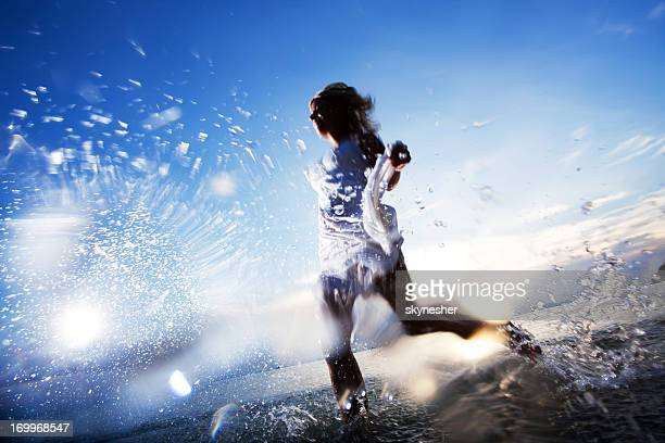 Young lady jogging in the water.