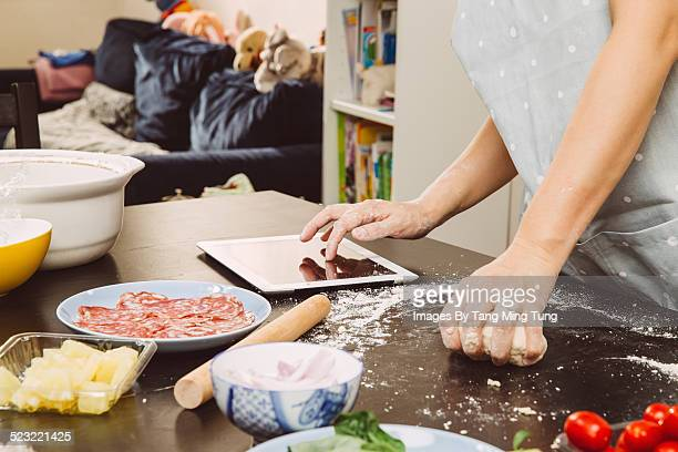 Young lady kneading dough on cooking table