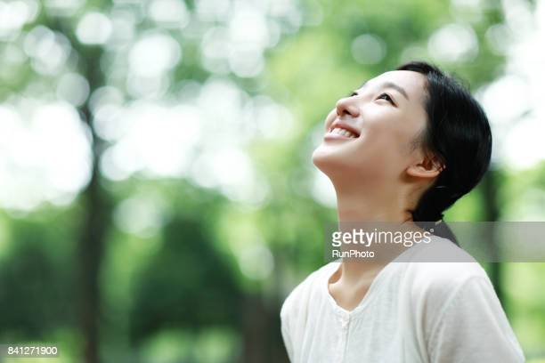 young lady laughing at the park - east asia stock pictures, royalty-free photos & images