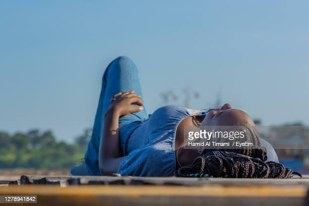 a young lady lies down on the floor with a view - mombasa stock pictures, royalty-free photos & images