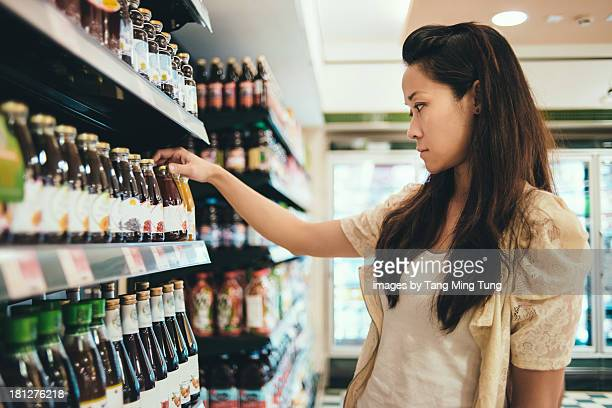 Young lady looking at labels on drinks in a store