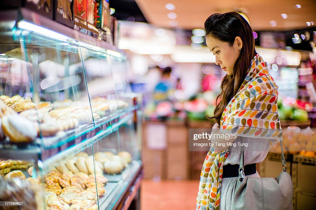Young lady looking at supermarket's bakery display : Stock Photo