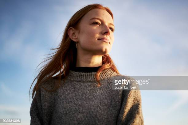 young lady looking content in the winter sunshine - wegkijken stockfoto's en -beelden
