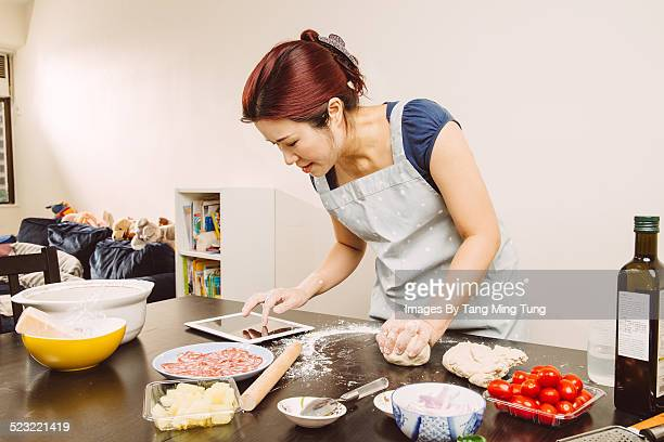 Young lady making pizza at home with tablet
