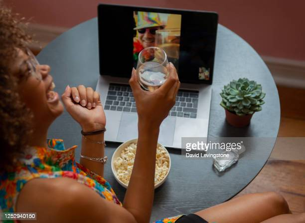 young lady on a video call to her friends celebrating gay pride at home. - young women stock pictures, royalty-free photos & images