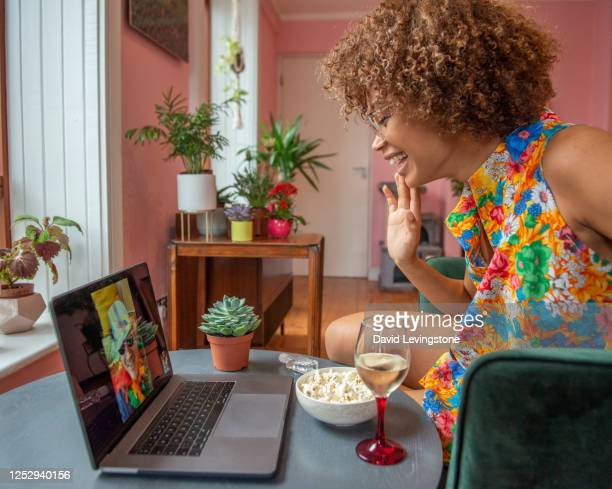 young lady on a video call to her friends celebrating gay pride at home. - happy hour stock pictures, royalty-free photos & images