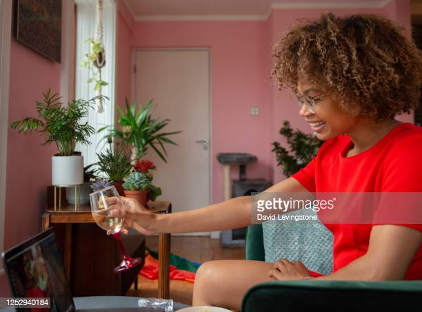 young lady on a video call to her friends celebrating gay pride at home. - emotion stock pictures, royalty-free photos & images