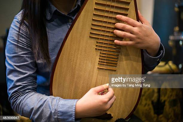 Young lady playing a Pipa