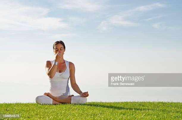 Young lady practising HathaYoga outdoor showing the pose anuloma viloma / nadi shodhana pranayama alternate nostril breathing
