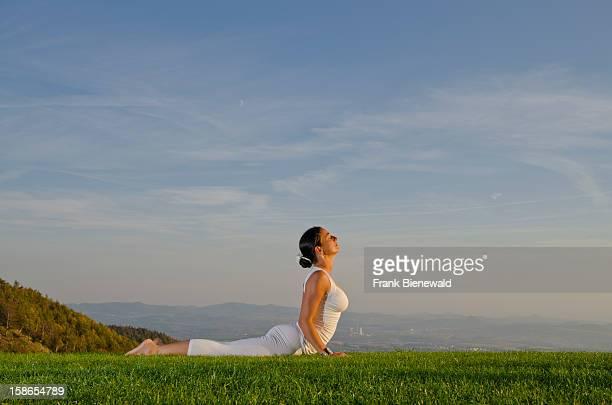 Young lady practising HathaYoga outdoor showing the pose bhujangasana cobra pose