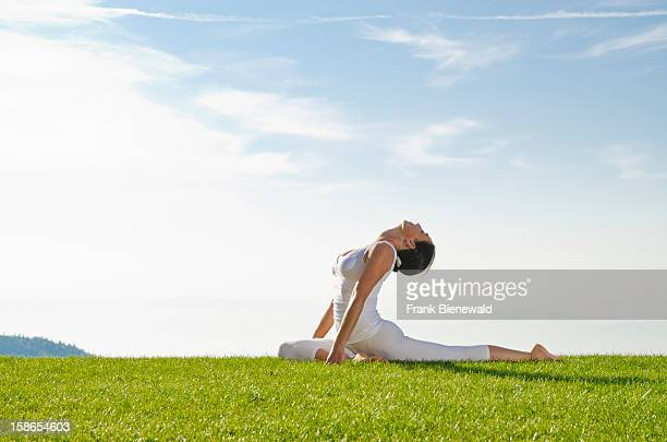 Young lady practising HathaYoga outdoor showing the pose kapotasana dove pose / pigeon pose