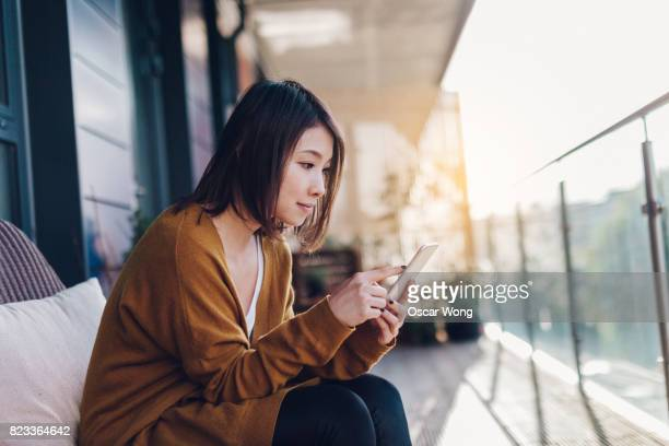 young lady reading message on mobile phone in balcony - surfing the net stock pictures, royalty-free photos & images