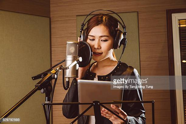 young lady recording vocals in studio - sound recording equipment stock pictures, royalty-free photos & images