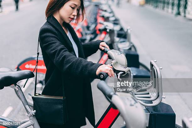 Young lady renting bicycle on street