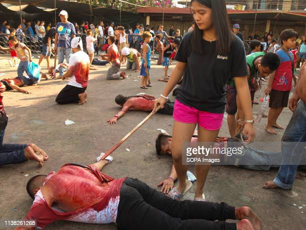 A young lady seen serving as an executioner to a flagellate crawling on the pavement during Good Friday Devout catholics in the deeply religious...