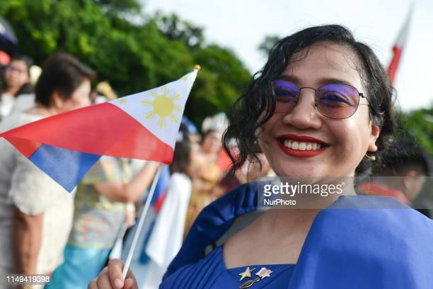 Young lady seen with a national flag during the 121st Independence Day celebrations at the Rizal monument in Manila, led by the Vice President of the...