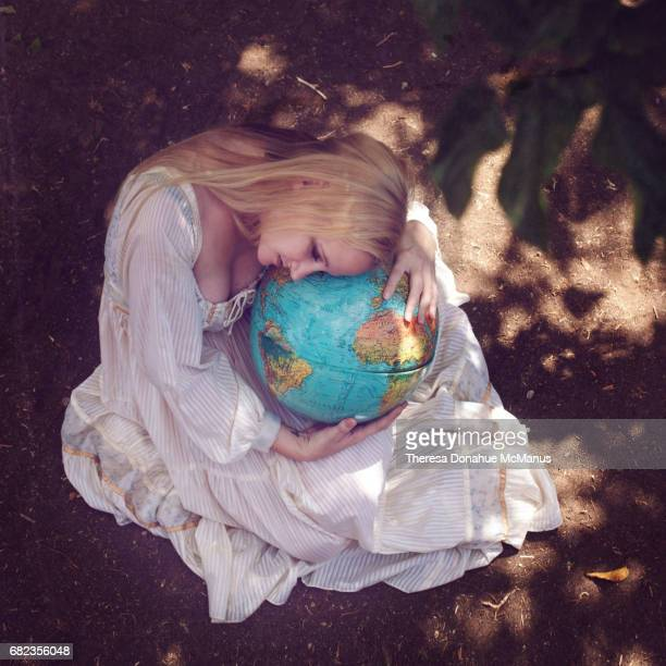 Young lady sits and holds and hugs a globe in her arms