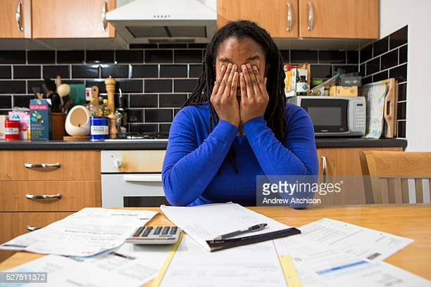 A young lady sits at her kitchen table at home checking over the household bills Dealing with debt Household utility bills making it difficult for a...
