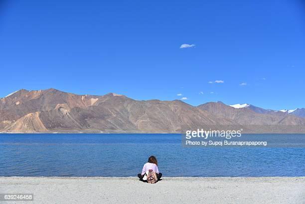 Young lady sitting beside the Pangong Lake or Pangong Tso , Leh ladakh , India