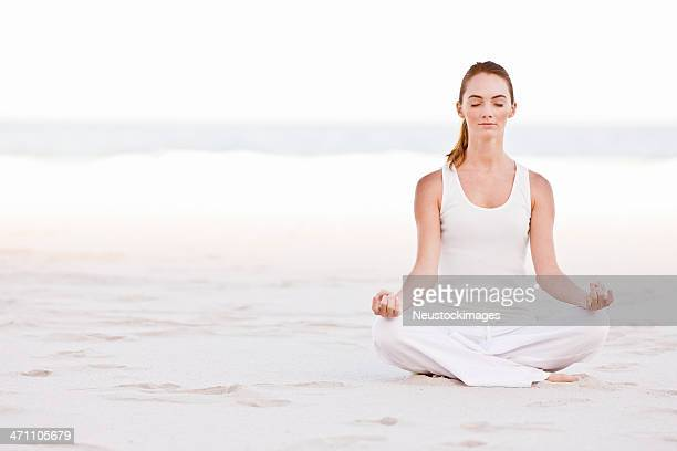 Young lady sitting in lotus position on beach