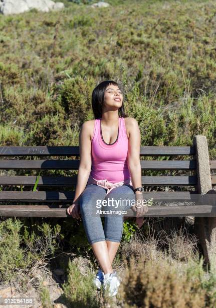 young lady sitting on a bench absorbing the sun. - western cape province stock pictures, royalty-free photos & images
