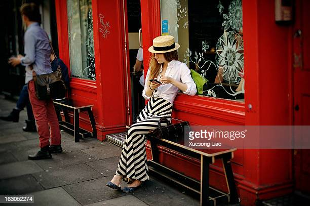 Young lady, sitting on bench, outside coffee shop,wondering,girl with phone,girl wearing hat,black&white striped skirt,red shop front,shop...