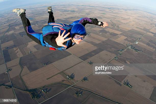 Young lady skydiving whilst mid-air waving to camera