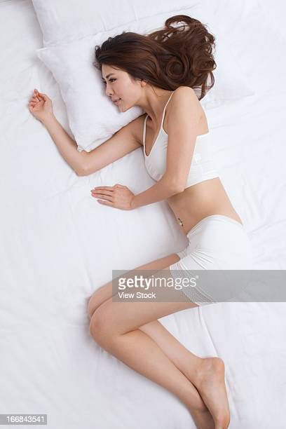 young lady sleeping on bed - lying on side stock pictures, royalty-free photos & images