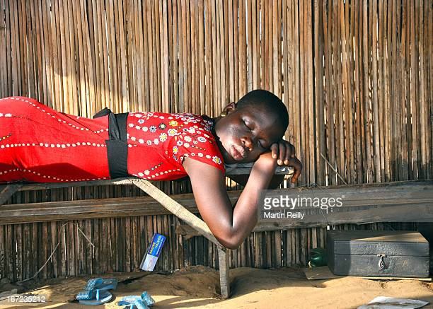 CONTENT] A young lady sleeps in shade out of the afternoon sun She works in a roadside bar next to the mechanics workshop She has kicked off her flip...
