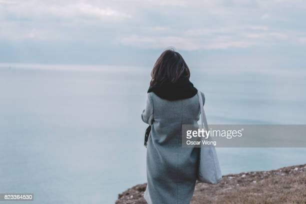 young lady standing on cliff and looking out to sea - seven sisters cliffs stock photos and pictures