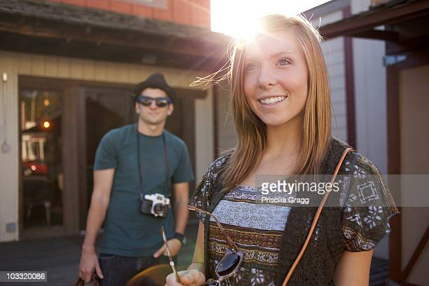 young lady stands in foreground with her boyfriend in the background. - julian california stock photos and pictures