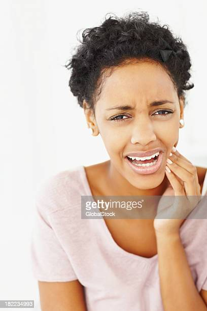 Junge Frau, die unter Zahnschmerz