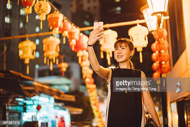 Young lady taking selfie on street at night