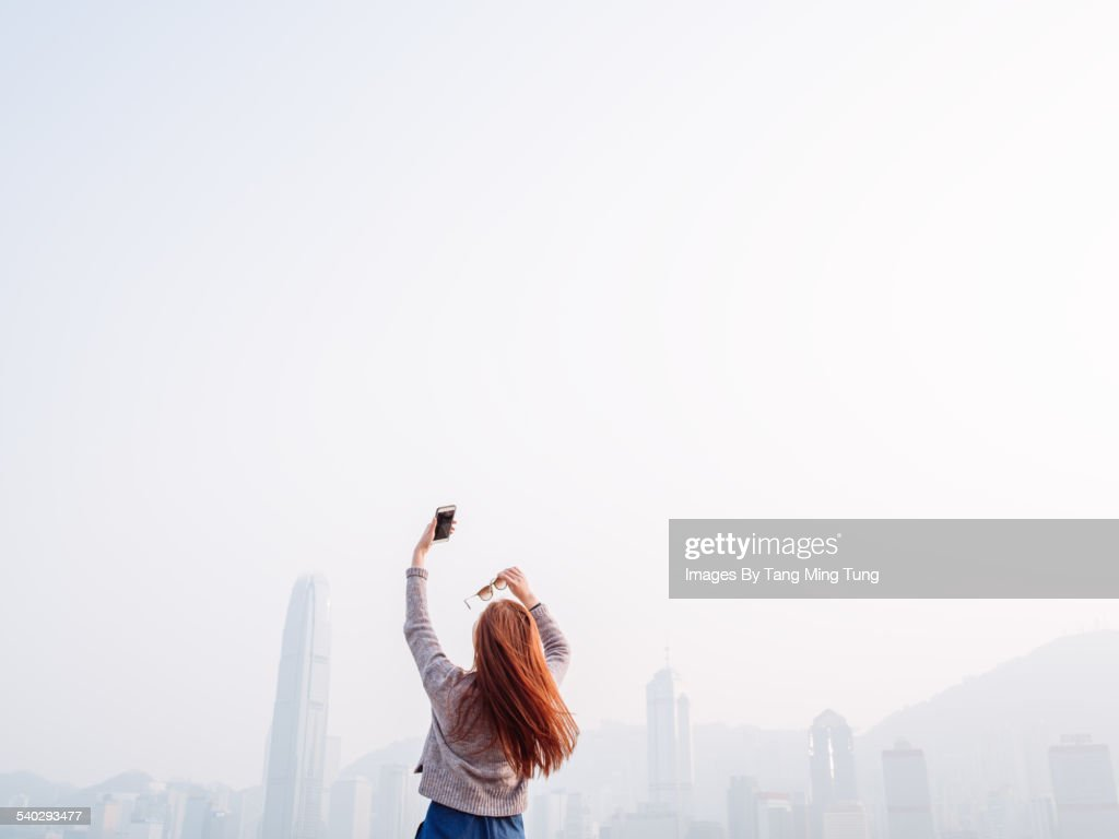 Young lady taking selfies in promenade joyfully : Stock-Foto
