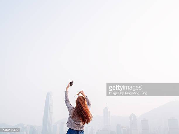 young lady taking selfies in promenade joyfully - rear view photos stock photos and pictures